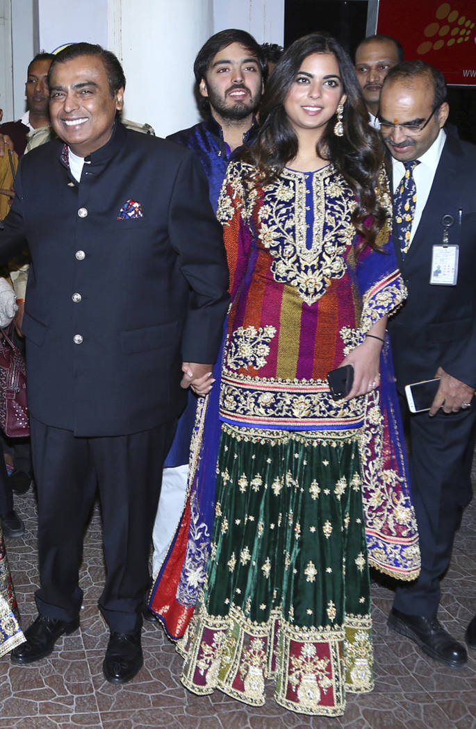 FILE - In this Friday, Nov. 30, 2018 file photo, Chairman of Reliance Industries Mukesh Ambani, left, and his daughter Isha Ambani, arrive to attend the wedding of Bollywood actress Priyanka Chopr ...
