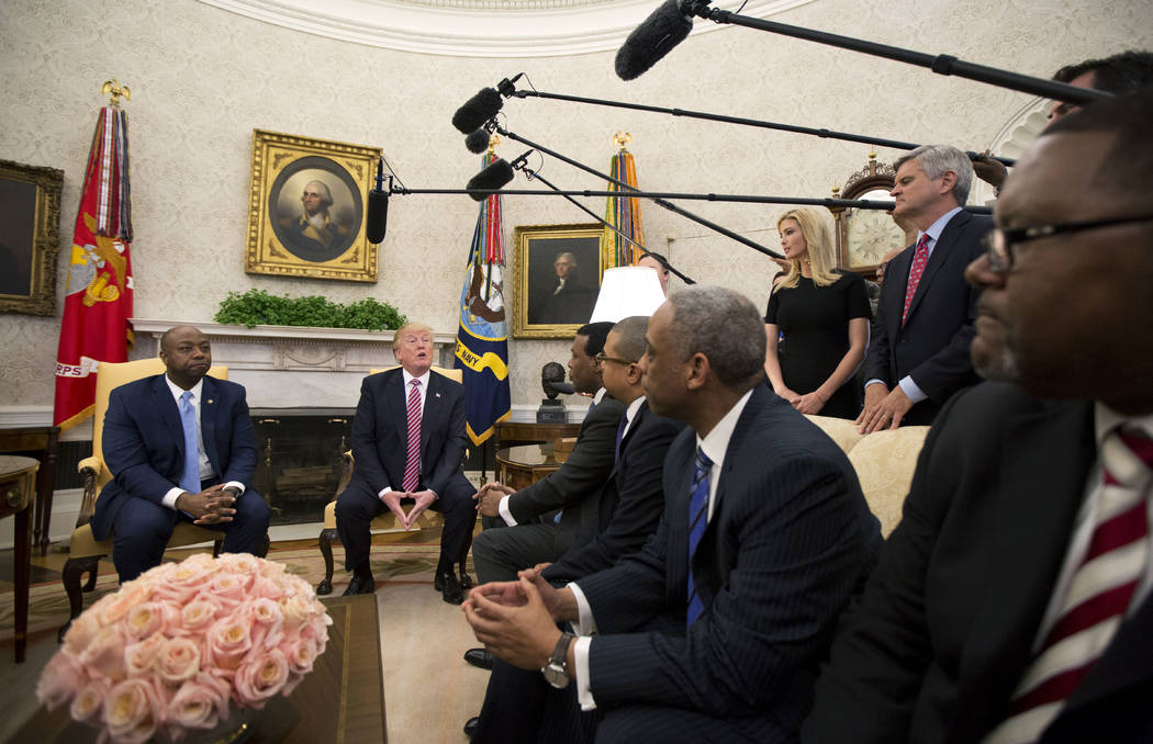 President Donald Trump, with Sen. Tim Scott, R-S.C., left, Ivanka Trump, top second from right, and Steve Case, top right, participate in a working session regarding the opportunity zones provided ...