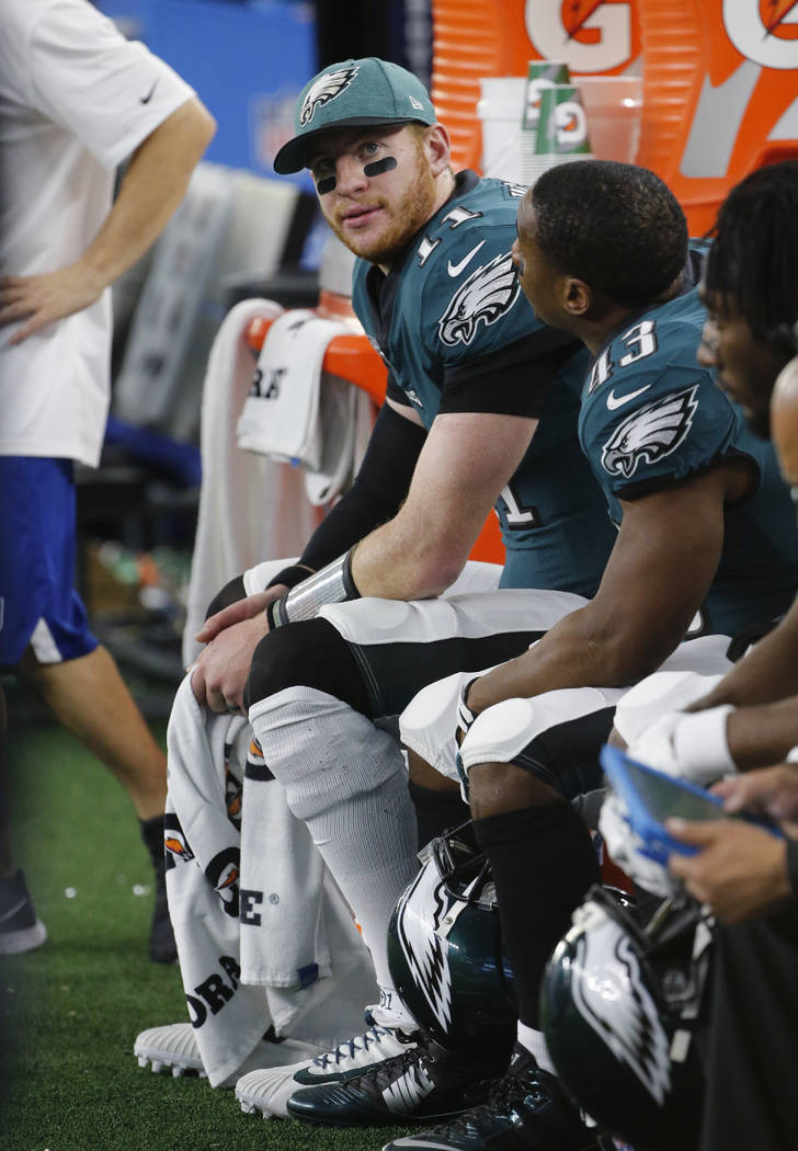 Philadelphia Eagles quarterback Carson Wentz (11) sits on the bench during the first half of an NFL football game against the Dallas Cowboys, in Arlington, Texas, Sunday, Dec. 9, 2018. (AP Photo/M ...