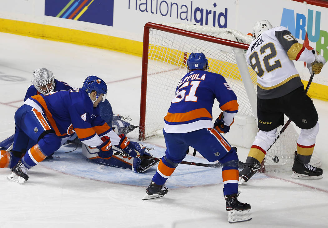 Vegas Golden Knights left wing Tomas Nosek (92) scores a goal against New York Islanders goaltender Robin Lehner, defenseman Thomas Hickey (4) and center Valtteri Filppula (51) during the third pe ...