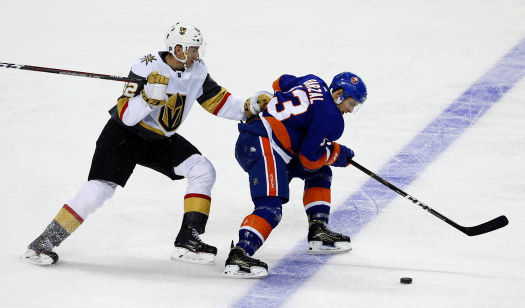 New York Islanders center Mathew Barzal (13) plays the puck against Vegas Golden Knights left wing Tomas Nosek (92) during the third period of an NHL hockey game, Wednesday, Dec.12, 2018, in New Y ...