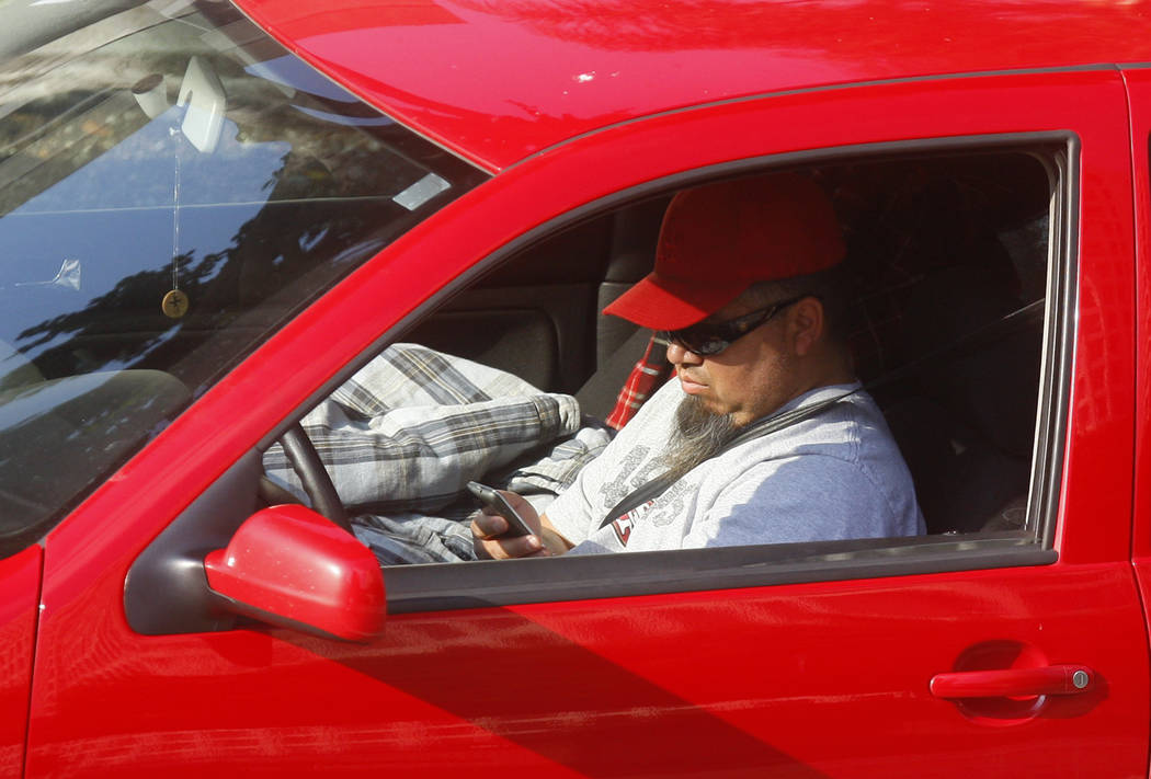 FILE - In this Dec. 14, 2011 file photo, a driver uses a cellphone while driving in Los Angeles. California regulators are considering a plan to charge a fee for text messaging on mobile phones t ...