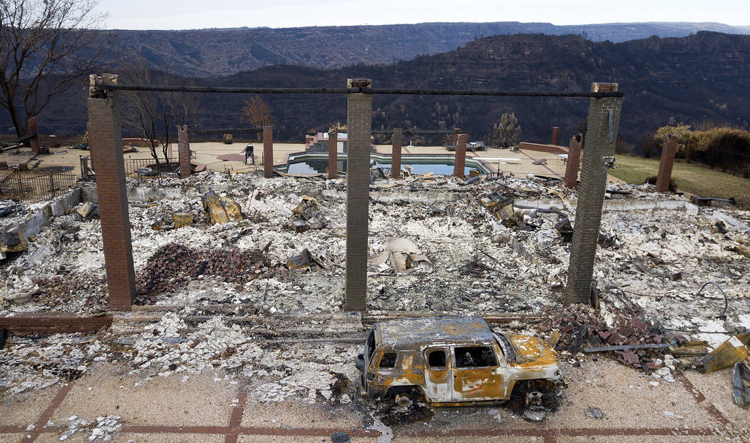 A vehicle rests in front of a home leveled by the Camp Fire in Paradise, Calif. on Dec. 3, 2018. Authorities estimate it will cost at least $3 billion to clear debris of 19,000 homes destroyed by ...