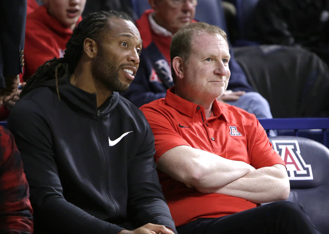 Arizona Cardinals player Larry Fitzgerald and Phoenix Suns owner Robert Sarver watch an NCAA college basketball game between Arizona and Connecticut on Thursday, Dec. 21, 2017, in Tucson, Ariz. Ar ...
