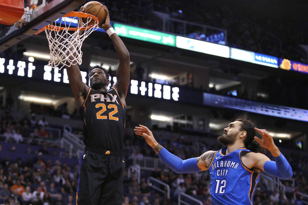 Phoenix Suns center Deandre Ayton (22) drives past Oklahoma City Thunder center Steven Adams during the first half during an NBA basketball game Saturday, Nov. 17, 2018, in Phoenix. (AP Photo/Rick ...
