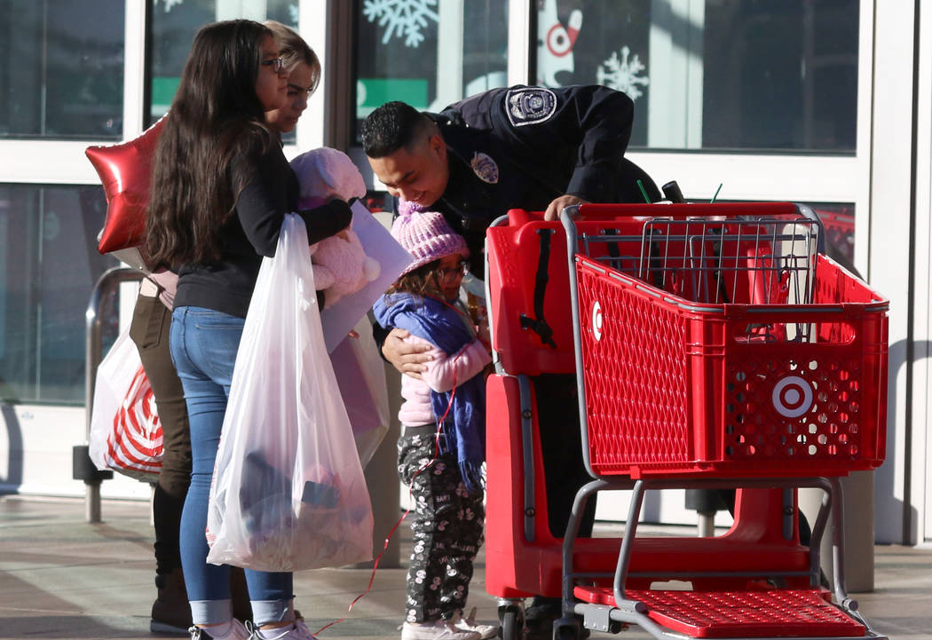 """North Las Vegas police officer Omar Camarena hugs Luna Avila, 5, after shopping during the annual ''Shop with Cop"""" event at Target at 7090 N. Fifth St., as Luna's mother, Rosaura Arvarez, and her ..."""