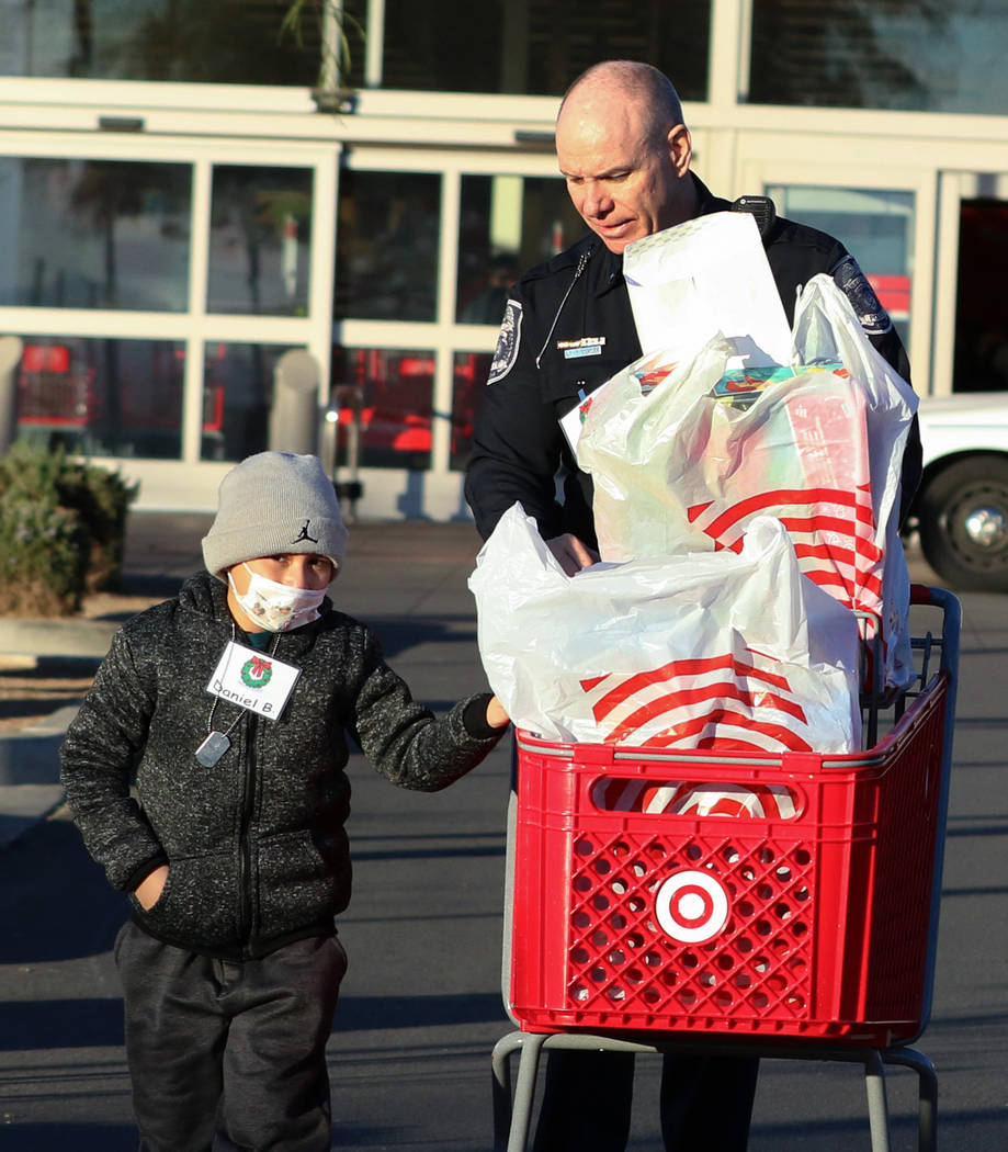 """Daniel Borrayo, 6, and North Las Vegas police Lt. Tom Glaizer leave after shopping at Target during the annual ''Shop with a Cop"""" event at 7090 N. Fifth St. on Wednesday, Dec. 12, 2018, in La ..."""