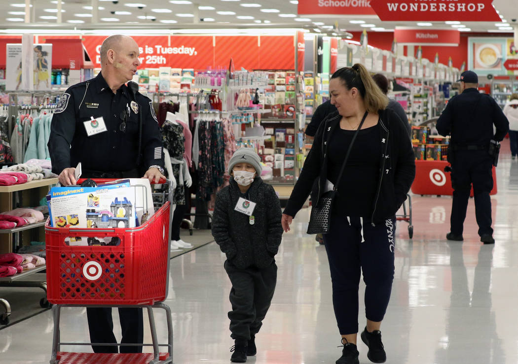 """Daniel Borrayo, 6, and and his mother Ariana Ortega shop with North Las Vegas police Lt. Tom Glaizer, left, during the annual ''Shop with a Cop"""" event at Target at 7090 N. Fifth St. on Wednes ..."""