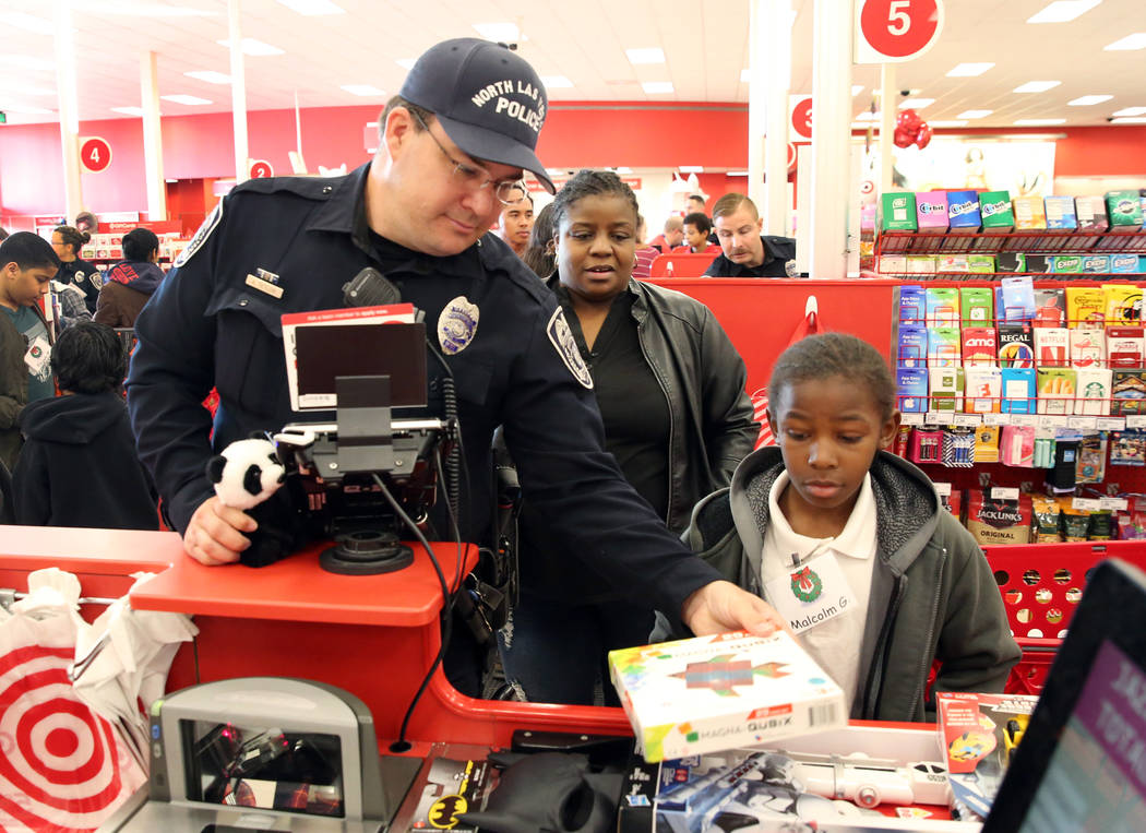 """Malcom Green, 9, and his mother, Rosalinda Williams, check out after shopping with North Las Vegas police officer A. Tetlow during the annual ''Shop with a Cop"""" event at Target at 7090 N. Fifth St ..."""