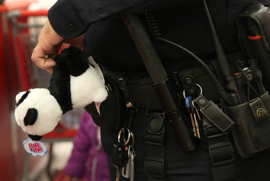 North Las Vegas police officer A. Tetlow holds a mini panda bear as he checks out after shopping with Malcom Green, 9, and his mother Rosalinda Williams, not photographed, during the annual ''Shop ...
