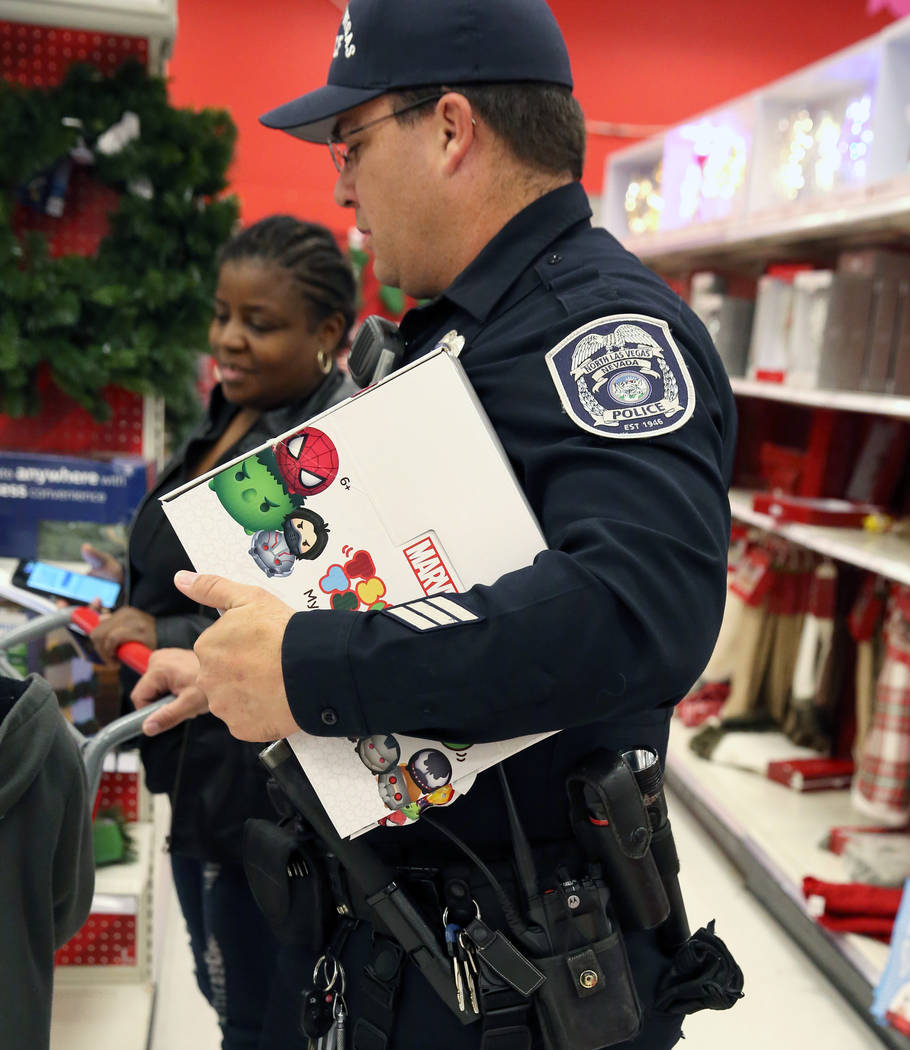 North Las Vegas police officer A. Tetlow checks out after shopping with Malcom Green, 9, not photographed, and Green's mother, Rosalinda Williams, left, after shopping during the annual ''Shop wit ...