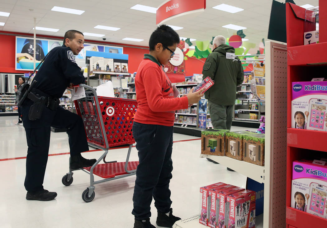 """Leonardo Zapera, 10, shops with North Las Vegas police officer D. Nardi, left, during the annual ''Shop with a Cop"""" event at Target at 7090 N. Fifth St. on Wednesday, Dec. 12, 2018, in Las Ve ..."""