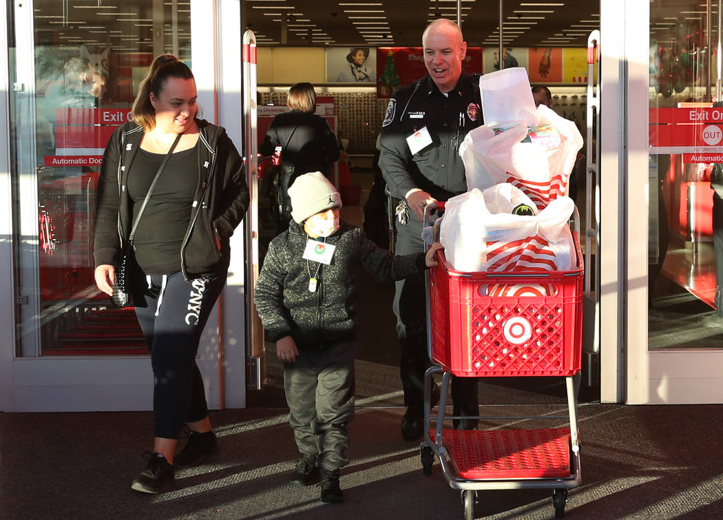 """Daniel Borrayo, 6, and and his mother, Ariana Ortega, leave after shopping at Target with North Las Vegas police Lt. Tom Glaizer, right, during the annual ''Shop with a Cop"""" event at 7090 N. Fifth ..."""