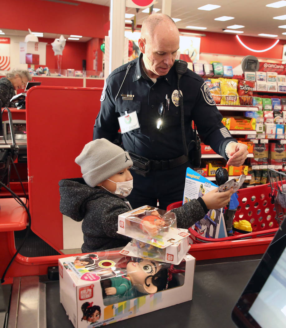 """Daniel Borrayo, 6, and North Las Vegas police Lt. Tom Glaizer check out after shopping during the annual ''Shop with a Cop"""" event at Target at 7090 N. Fifth St. on Wednesday, Dec. 12, 2018, i ..."""