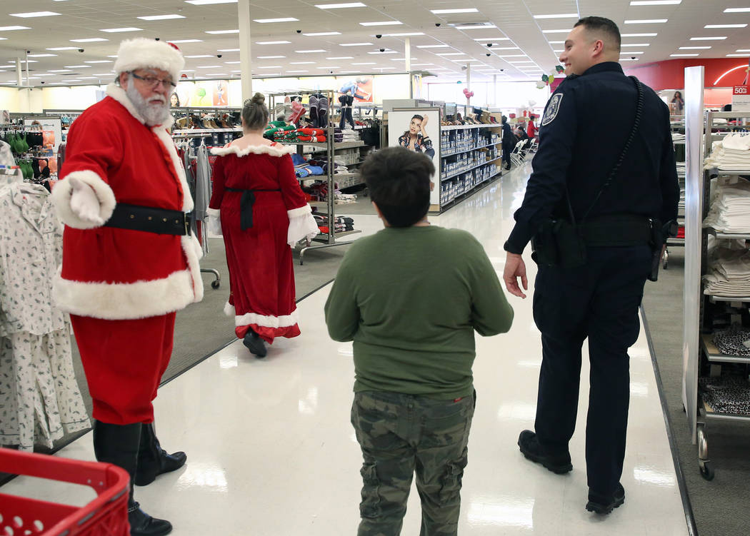 """Nikolas Davison, 12, center, chats with Santa as he shops with North Las Vegas police officer Robert Ramirez, right, during the annual ''Shop with a Cop"""" event at Target at 7090 N. Fifth St. ..."""