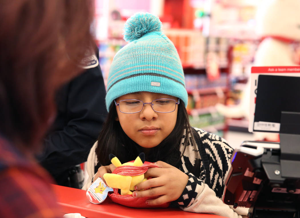 """Emelin Bautista, 10, checks out after shopping with North Las Vegas police officer Spencer Kinney, not photographed, during the annual ''Shop with a Cop"""" event at Target at 7090 N. Fifth St. ..."""