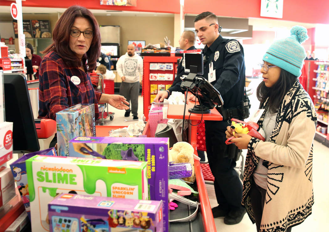 """Emelin Bautista, right, 10, checks out after shopping with North Las Vegas police officer Spencer Kinney during the annual ''Shop with a Cop"""" event at Target at 7090 N. Fifth St. on Wednesday ..."""