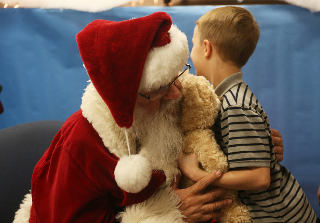 Santa Claus gives Zachary Cables, 7, a hug at the Build-A-Bear-Workshop at Doris Reed Elementary School in Las Vegas, Thursday, Dec. 13, 2018. Rachel Aston Las Vegas Review-Journal @rookie__rae