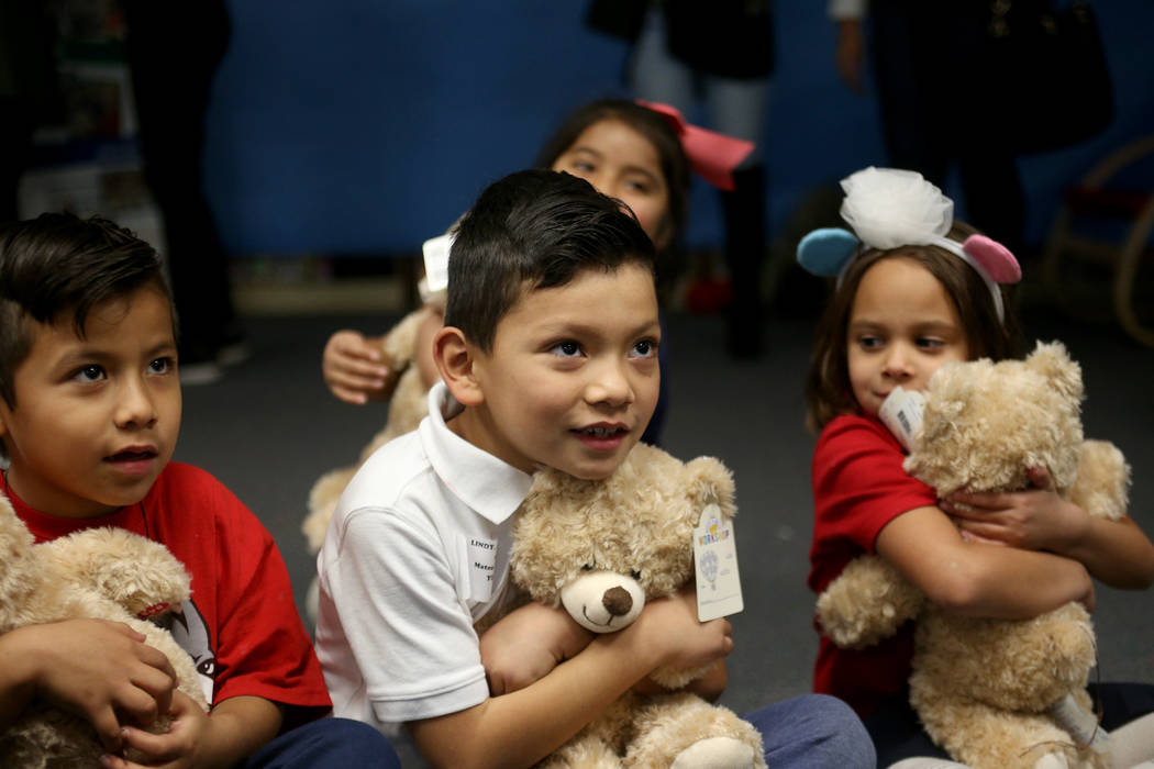 Alesky Rubio Roa, 6, from left, Mateo Lopez, 6, and Sophia Hopper, 6, hug their stuff bears, at the Build-A-Bear-Workshop at Doris Reed Elementary School in Las Vegas, Thursday, Dec. 13, 2018. Rac ...