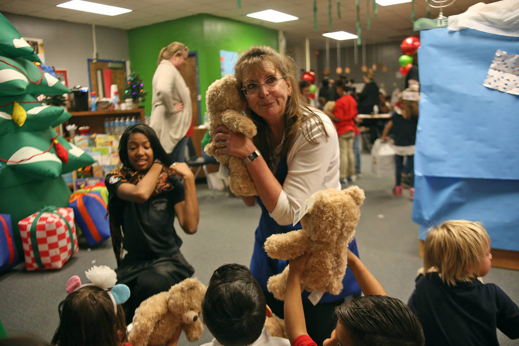 Julie Hayes, district manager for Build-A-Bear, pretends to hear the bear talk for the students at the Build-A-Bear-Workshop at Doris Reed Elementary School in Las Vegas, Thursday, Dec. 13, 2018. ...