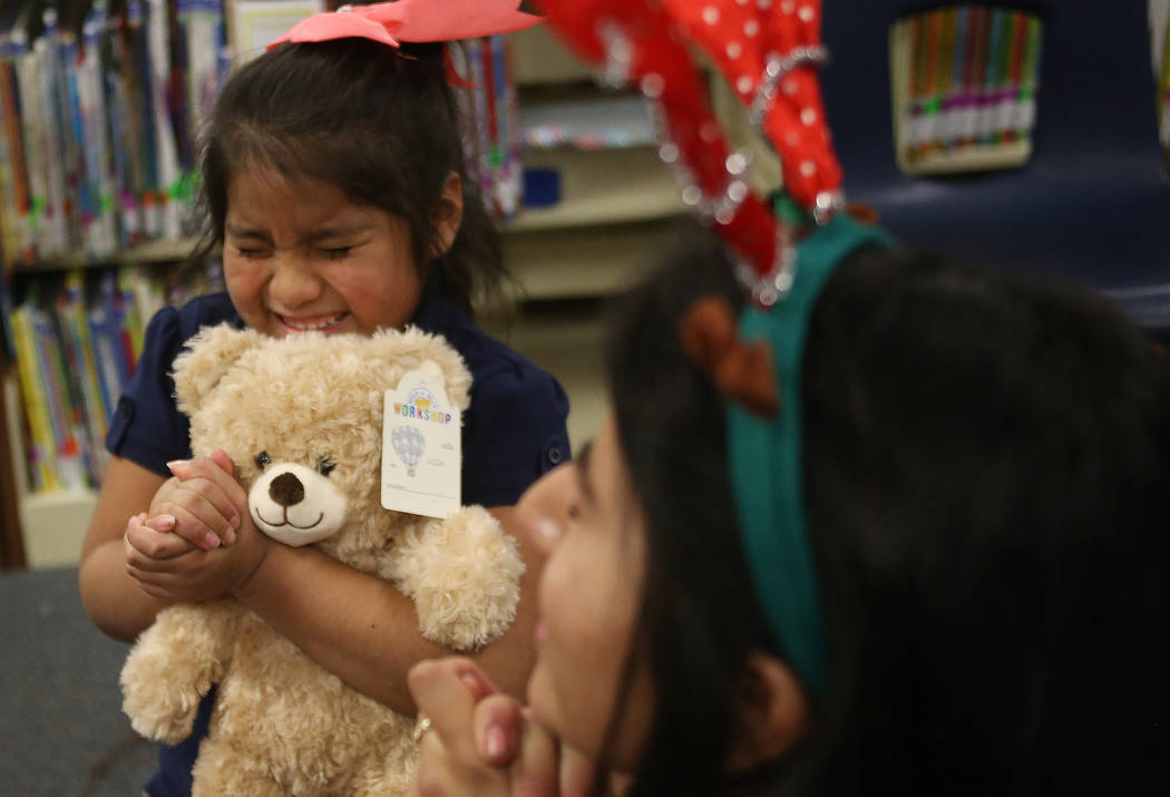 Lisbeth Ramon San Pedro, 7, hugs her bear with the heart in her hands before putting it inside the bear at the Build-A-Bear-Workshop at Doris Reed Elementary School in Las Vegas, Thursday, Dec. 13 ...