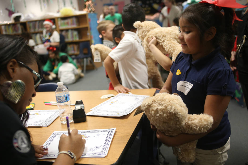 Please Johnson, with Americorp, helps Lisbeth Ramon San Pedro with her stuffed bear's birth certificate at the Build-A-Bear-Workshop at Doris Reed Elementary School in Las Vegas, Thursday, Dec. 13 ...