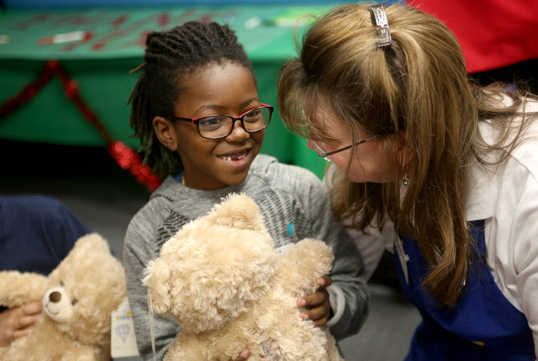 Jeremiah Cooper, 6, waits with his stuffed bear and Julie Hayes, the district manager for Build-A-Bear, at the Build-A-Bear-Workshop at Doris Reed Elementary School in Las Vegas, Thursday, Dec. 13 ...