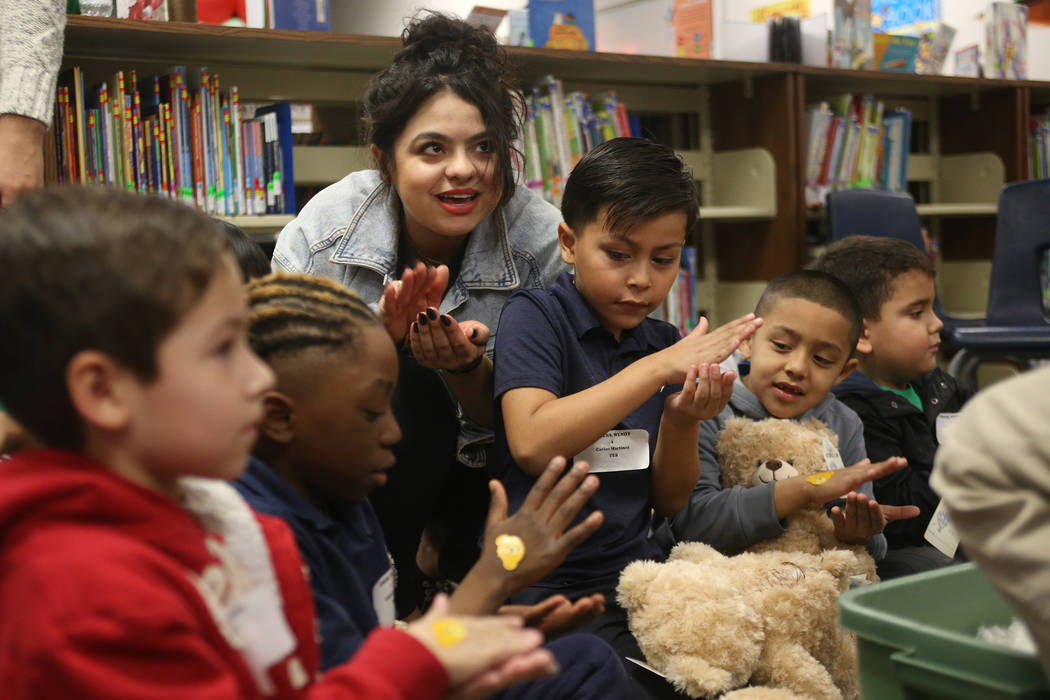 Volunteer Lilybeth Molina helps students prepare the stuffed heart for their bears at the Build-A-Bear-Workshop at Doris Reed Elementary School in Las Vegas, Thursday, Dec. 13, 2018. Rachel Aston ...
