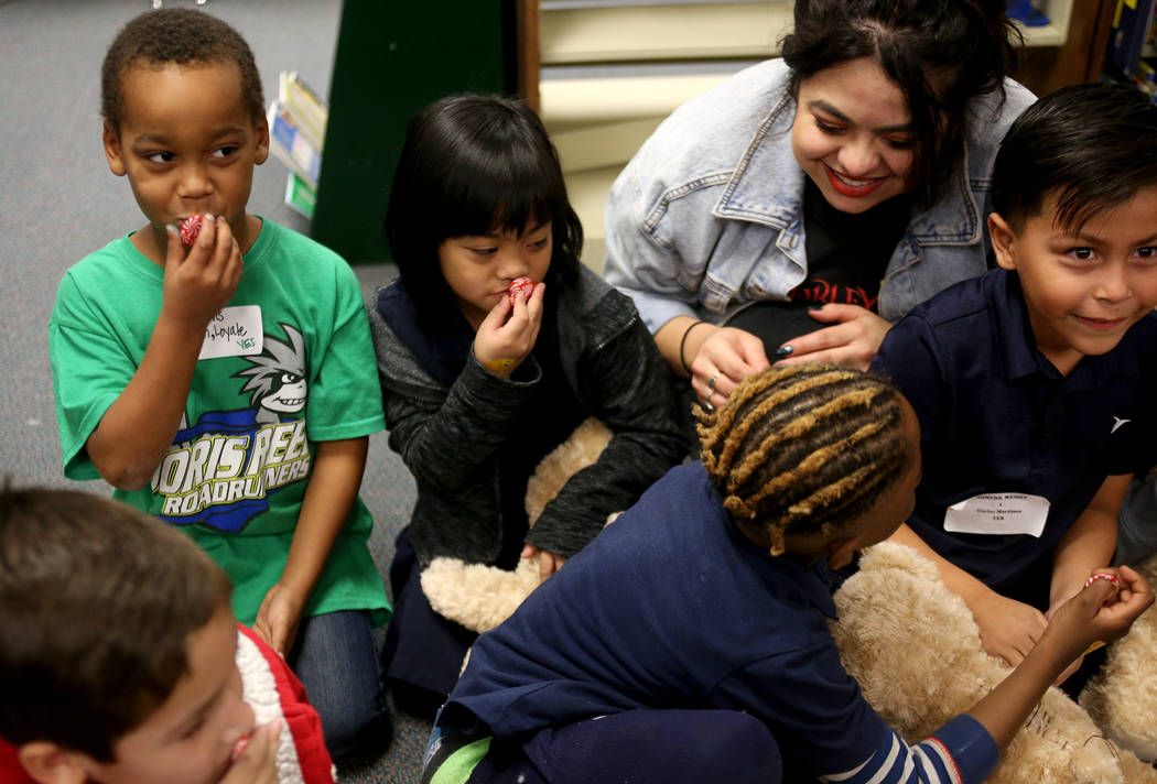 Loyale Franklin, 6, from left, Rhaelyn Mendoza, 6, volunteer Lilybeth Molina, and Carlos Martinez, 6, prepare the stuffed heart for their bears at the Build-A-Bear-Workshop at Doris Reed Elementar ...