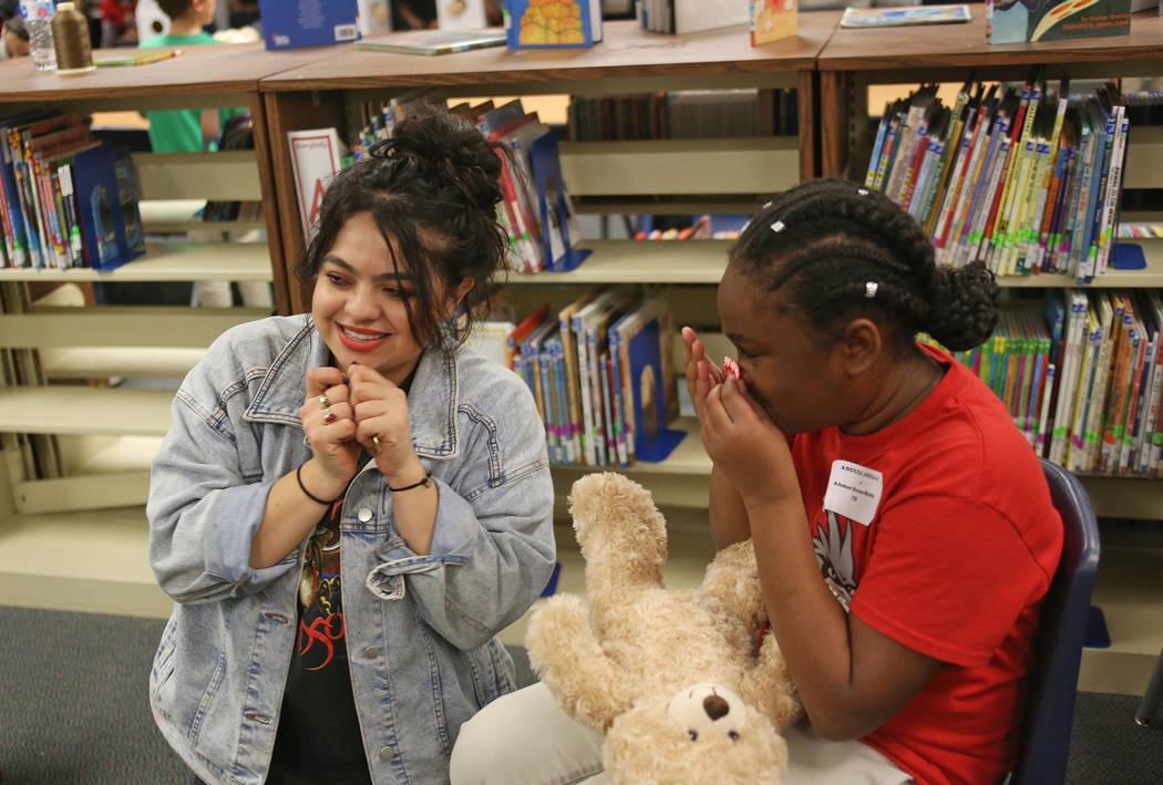 Volunteer Lilybeth Molina helps Ahmari Braxton-Shelby, 10, prepare the stuffed hearts for the bear at the Build-A-Bear-Workshop at Doris Reed Elementary School in Las Vegas, Thursday, Dec. 13, 201 ...