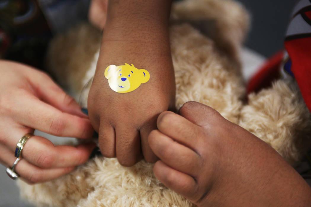 Volunteer Lilybeth Molina helps Ahmari Braxton-Shelby, 10, put the stuffed heart into her bear at the Build-A-Bear-Workshop at Doris Reed Elementary School in Las Vegas, Thursday, Dec. 13, 2018. R ...