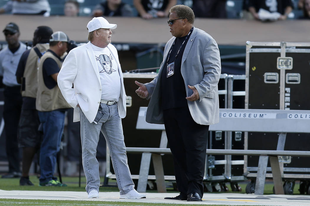 Oakland Raiders owner Mark Davis, left, talks with general manager Reggie McKenzie before an NFL preseason football game between the Raiders and the Detroit Lions in Oakland, Calif., Friday, Aug. ...