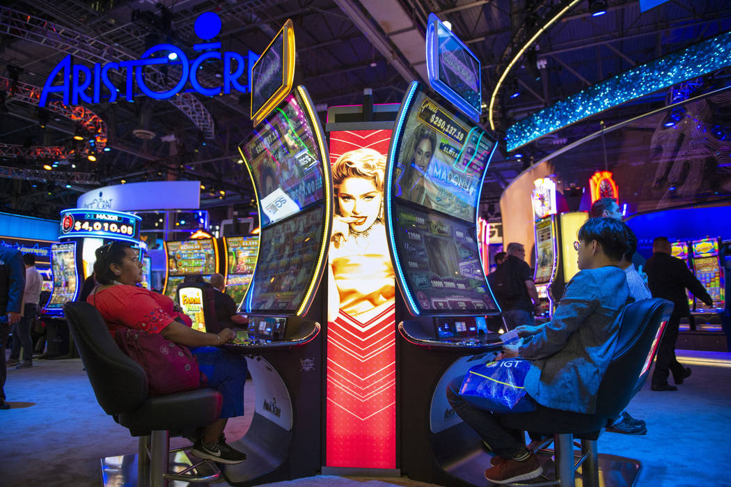 Attendees try out Madonna themed slot machines that feature a curved screen at the Aristocrat booth at the 18th annual Global Gaming Expo at Sands Expo and Convention Center in Las Vegas, Thursday ...