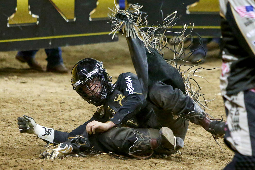 "Sage Kimzey of Strong City, Okla. (3) falls off of ""Joker"" while competing Bull Riding during the seventh go-round of the National Finals Rodeo at the Thomas & Mack Center in Las Veg ..."