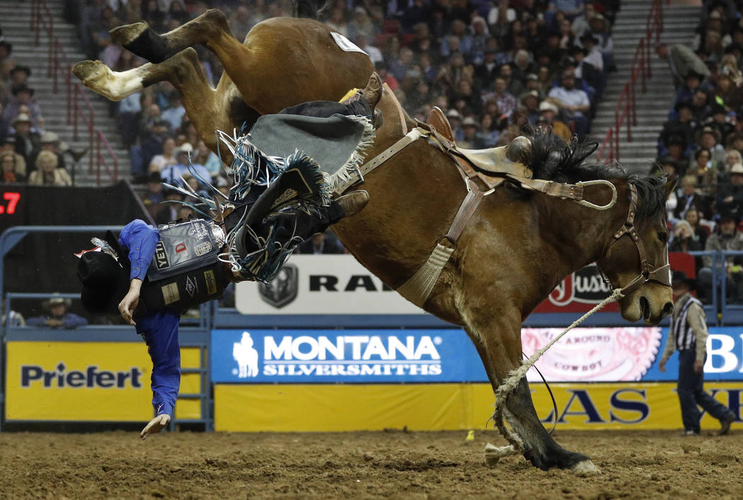 Ryder Wright, of Milford, Utah, is bucked off his horse while competing in the saddle bronc riding event during the seventh go-round of the National Finals Rodeo, Wednesday, Dec. 12, 2018, in Las ...