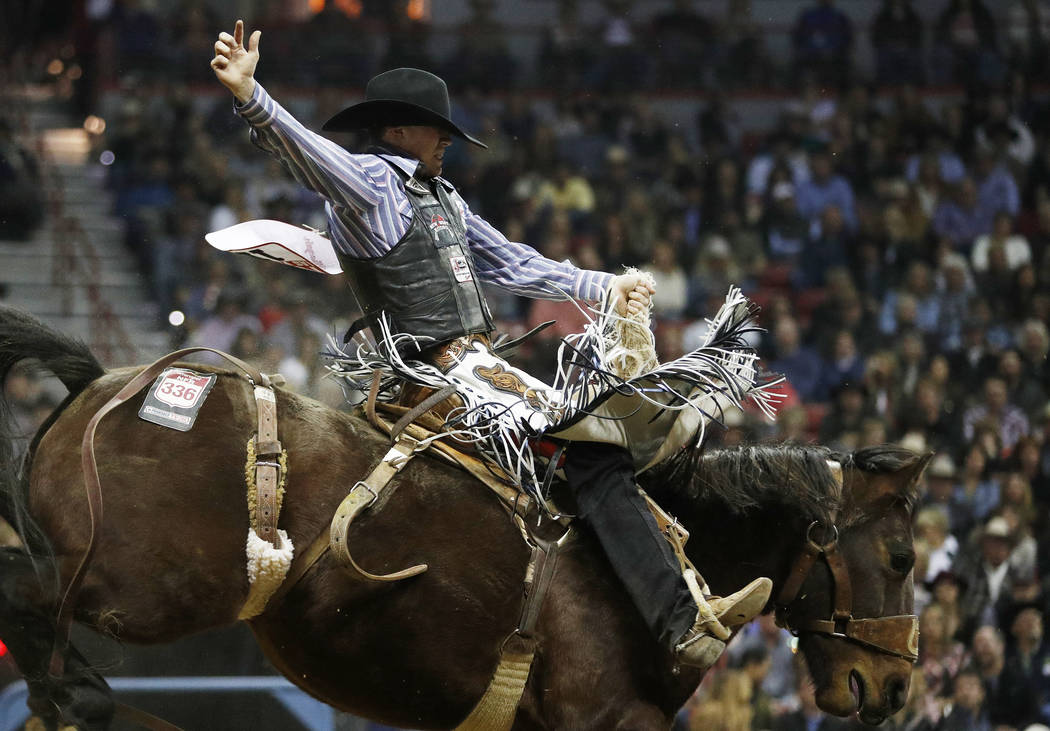 Chase Brooks, of Deer Lodge, Mont., competes in the saddle bronc riding event during the seventh go-round of the National Finals Rodeo, Wednesday, Dec. 12, 2018, in Las Vegas. (AP Photo/John Locher)