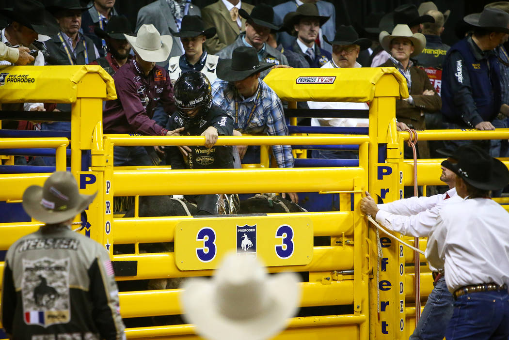 """Sage Kimzey of Strong City, Okla. (3) gets ready to ride """"Joker"""" while competing Bull Riding during the seventh go-round of the National Finals Rodeo at the Thomas & Mack Center in L ..."""