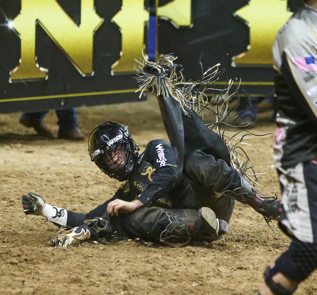 """Sage Kimzey of Strong City, Okla. (3) falls off of """"Joker"""" while competing Bull Riding during the seventh go-round of the National Finals Rodeo at the Thomas & Mack Center in Las Veg ..."""