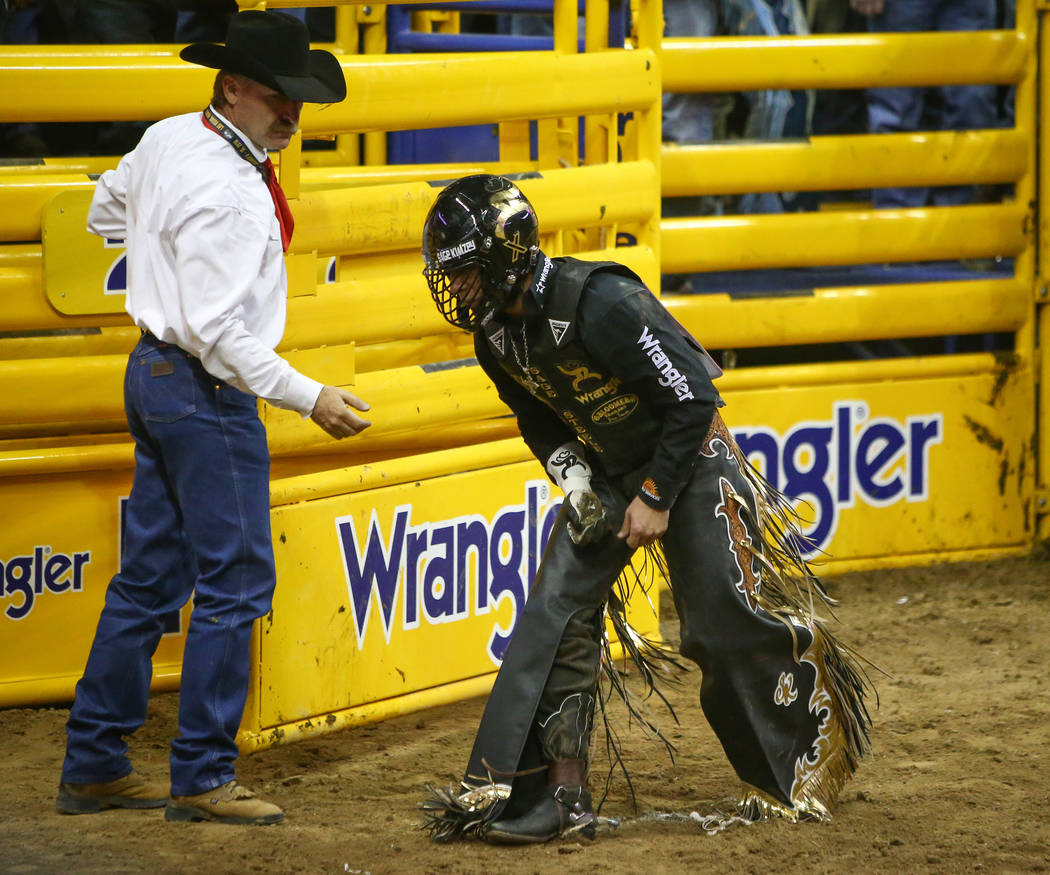 """Sage Kimzey of Strong City, Okla. (3) holds his hand after falling off of """"Joker"""" while competing Bull Riding during the seventh go-round of the National Finals Rodeo at the Thomas ..."""