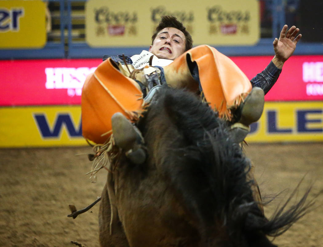 """Clayton Biglow of Clements, Calif. (10) rides """"Short Night"""" while competing bareback riding during the seventh go-round of the National Finals Rodeo at the Thomas & Mack Center in La ..."""
