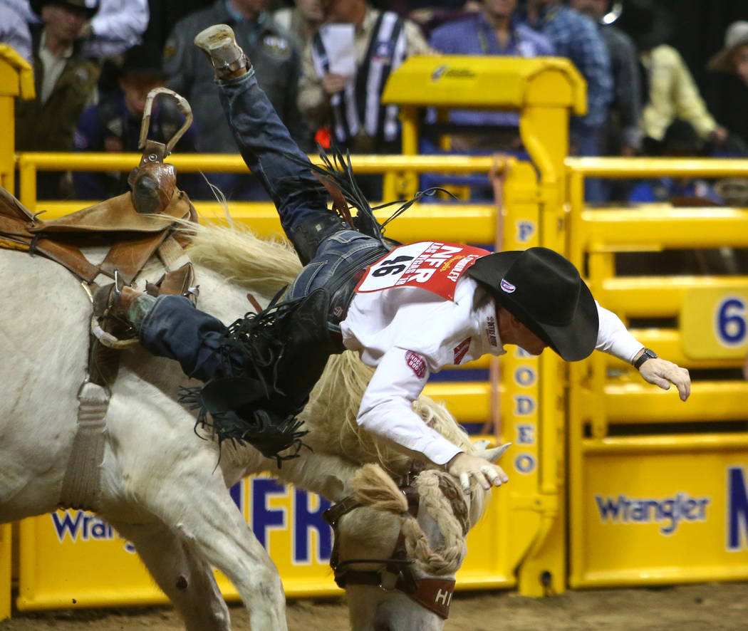 """Sterling Crawley of Stephenville, Texas (46) rides """"Garden City Gal"""" while competing in saddle bronc riding during the seventh go-round of the National Finals Rodeo at the Thomas & M ..."""