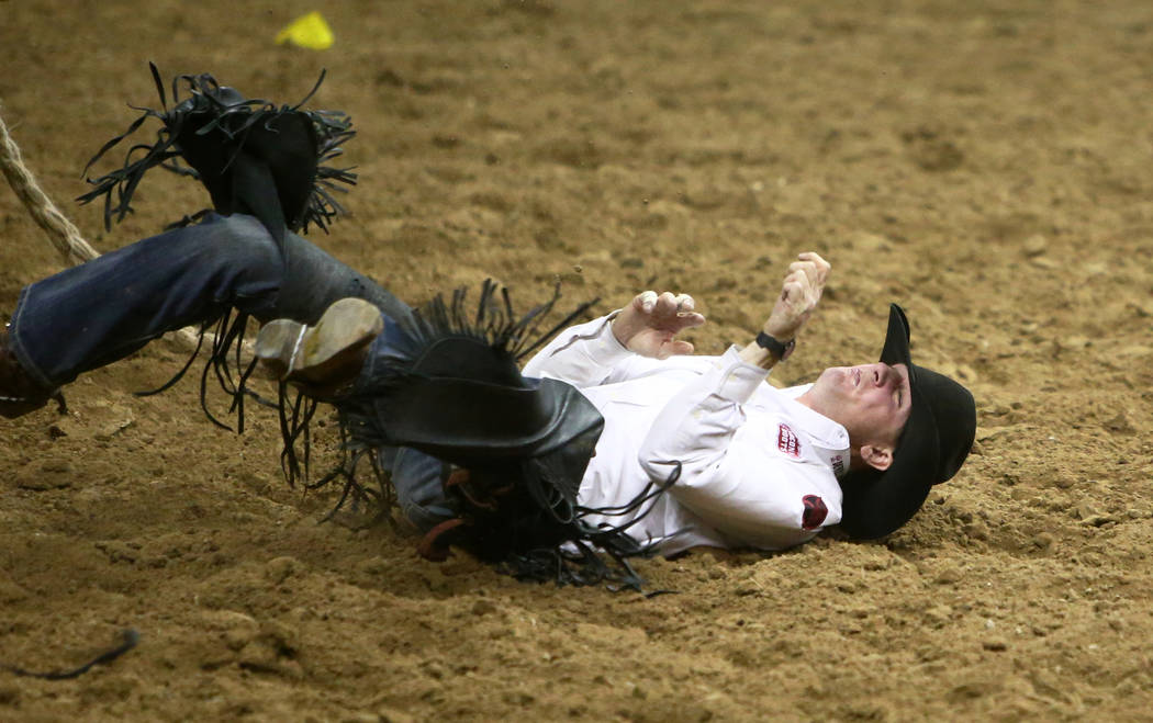 """Sterling Crawley of Stephenville, Texas (46) is thrown off by """"Garden City Gal"""" while competing in saddle bronc riding during the seventh go-round of the National Finals Rodeo at the Th ..."""