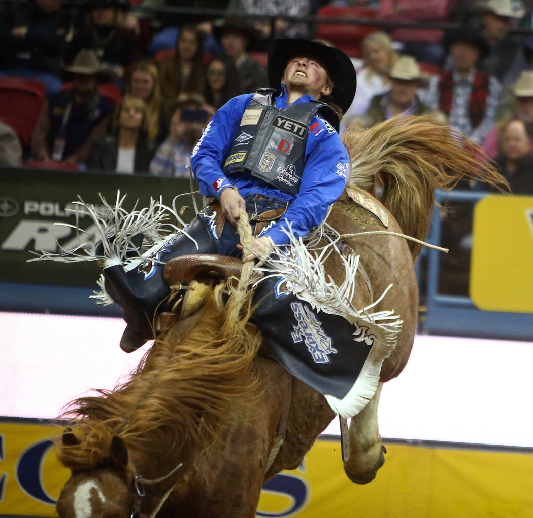 """Rusty Wright of Milford, Utah (20) rides """"Major Huckleberry"""" while competing saddle bronc riding during the seventh go-round of the National Finals Rodeo at the Thomas & Mack Center ..."""
