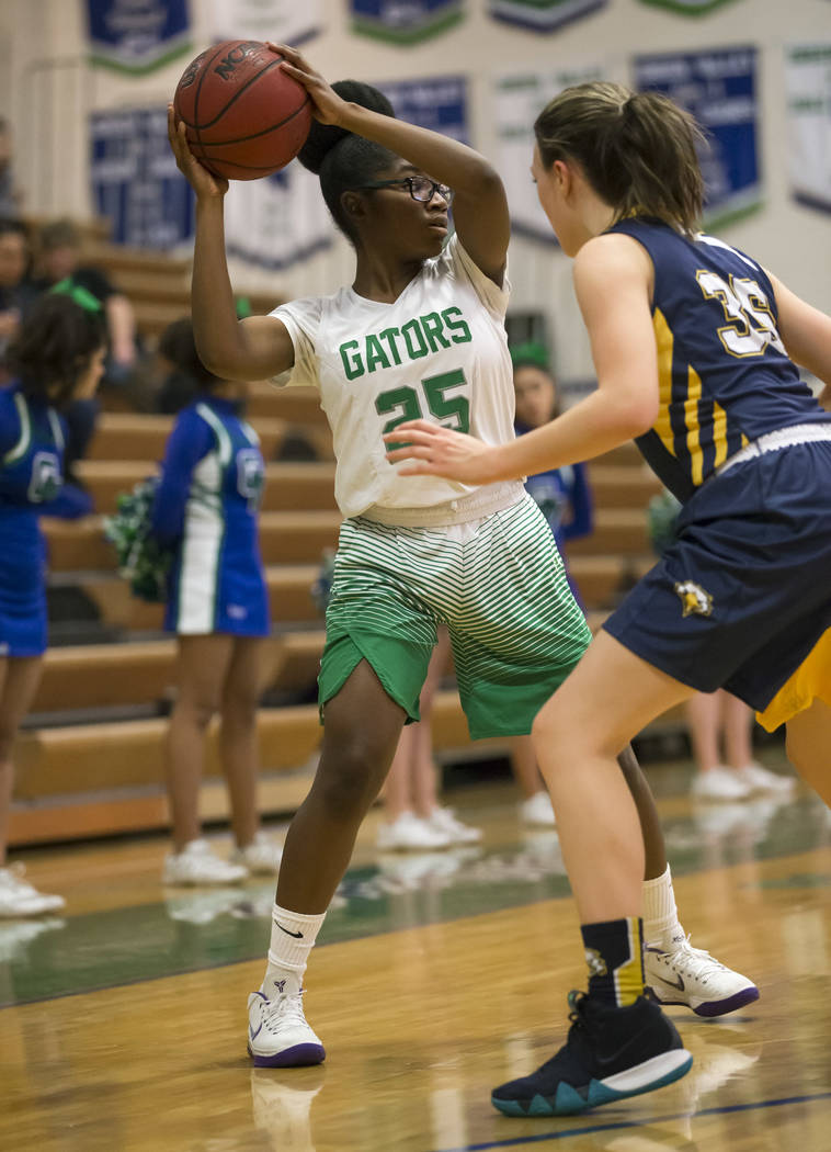 Green Valley's Alexis Mensah (25) looks to pass as Boulder City guard Hannah Estes (35) defends during the first half of a varsity basketball game at Green Valley High School in Henderson on Wedne ...