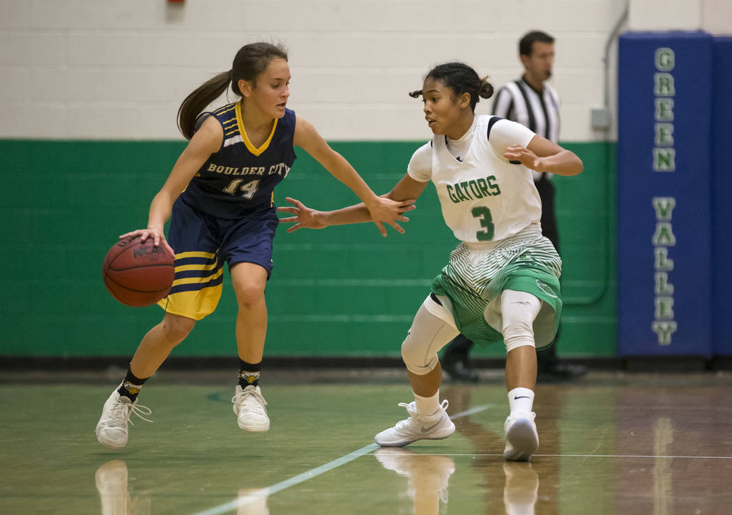 Boulder City's Samantha Bahde (4) dribbles the ball as Green Valley's Amore Espino (3) defends during the first half of a varsity basketball game at Green Valley High School in Henderson on Wednes ...