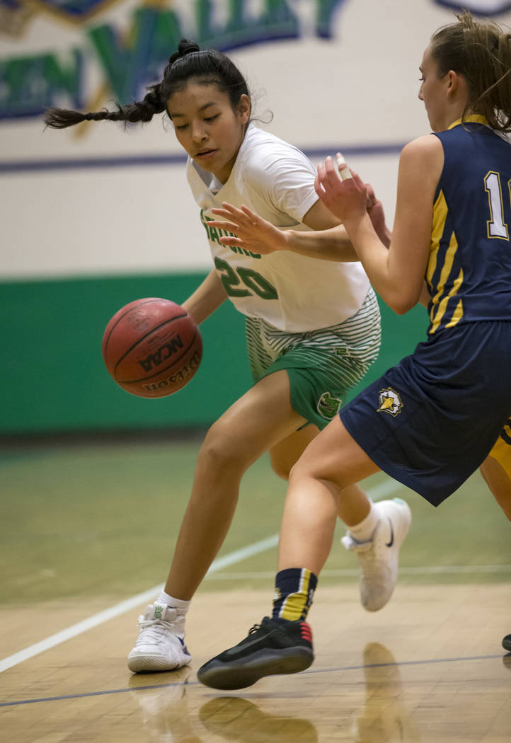 Green Valley's Michelle Lagunas-Monroy (20) drives the ball against Boulder City's Kailee Fisher (11) during the first half of a varsity basketball game at Green Valley High School in Henderson on ...