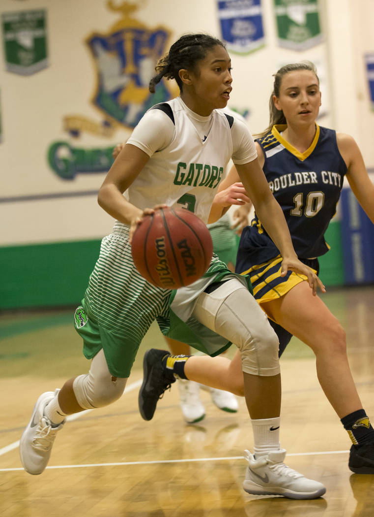 Green Valley's Amore Espino (3) dribbles the ball against Boulder City's Madison Manns (10) during the first half of a varsity basketball game at Green Valley High School in Henderson on Wednesday ...