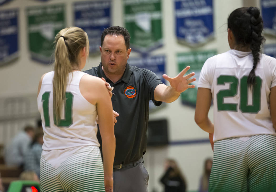 Green Valley's head coach Rey White talks with Julia Clark (10) and Michelle Lagunas-Monroy (20 ) on a time out during the second half of a varsity basketball game against Boulder City at Green Va ...