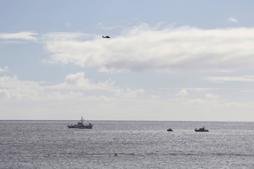 A U.S. Coast Guard helicopter flies over rescue boats at the scene of plane crash off Honolulu, Wednesday, Dec. 12, 2018. Federal Aviation Administration spokesman Ian Gregor said a Hawker Hunter ...