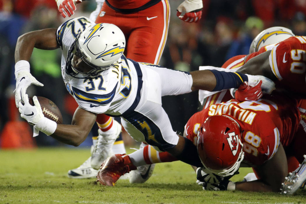 Los Angeles Chargers running back Justin Jackson (32) is tackled by Kansas City Chiefs tackle Xavier Williams (98) during the first half of an NFL football game in Kansas City, Mo., Thursday, Dec. ...